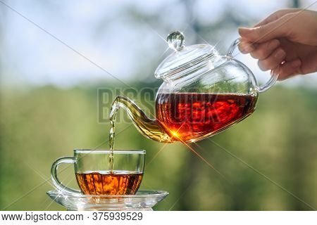 Woman Pours Tea From A Glass Teapot Into A Glass Cup. Tea Party In The Open Air. Close-up Of A Cup A