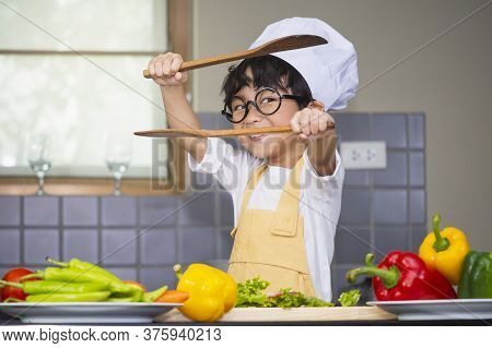 Asian Boy Son Cooking Salad Food Holdind Wooden Spoon With Vegetable Holding Tomatoes And Carrots, B