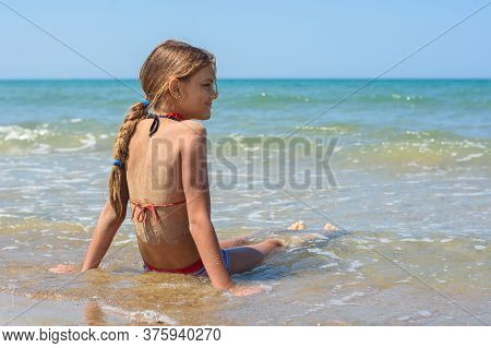 A Girl Of Ten Years Old Sits In The Water On The Sea Coast