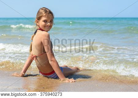 The Girl Sits On A Sandy Beach And Turned To Look In Frame