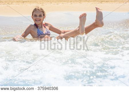 Girl Swims In The Waves On The Sandy Seashore