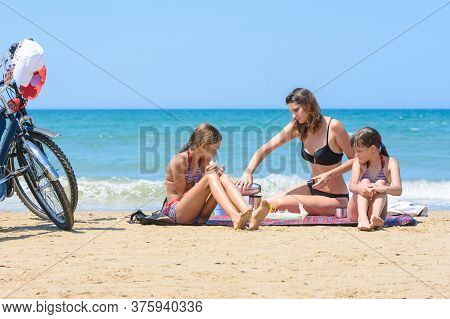 Children Watch Mom Pouring Mugs Of Tea On The Seashore On A Warm Summer Day