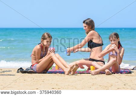 Children And Mom Eat While Sitting On The Seashore