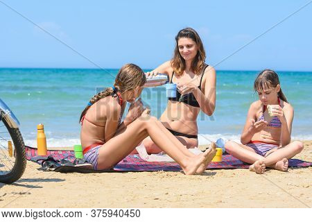 Mom Pours Tea From A Thermos, Children Eat Cooked Sandwiches, Having Lunch On The Sea Beach