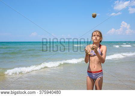 A Girl Of Ten Years Juggles Sand Balls On The Seashore