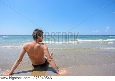 A Man Sits On The Seashore And Looks Into The Distance