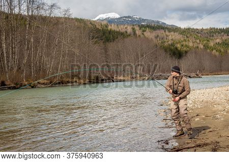 Kalum River, British Columbia, Canada - April 11th, 2017: A Fly Fisherman Hooked Into A Big Fish In