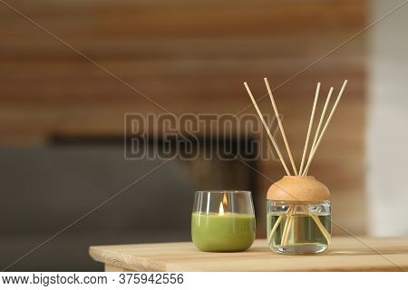 Aromatic Reed Air Freshener And Scented Candle On Table Indoors. Space For Text