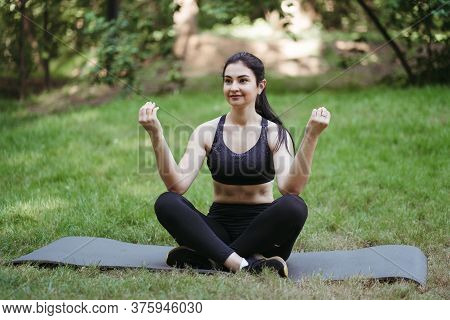 Outdoor Yoga. Young Woman Relaxing In Nature Park Meditating On Fitness Mat. Leisure, Self Developme