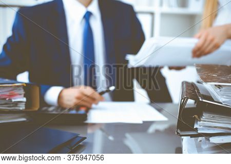 Binders With Papers Waiting To Be Processed With Businessman Or Bookkeeper Back In Blur. Accounting