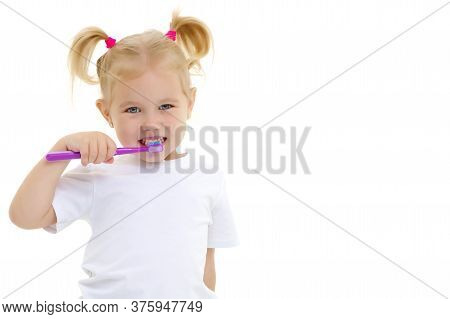 Cute Little Girl Brushing Her Teeth. She Uses A Toothbrush. The Concept Of Healthy Teeth, Hygiene, D