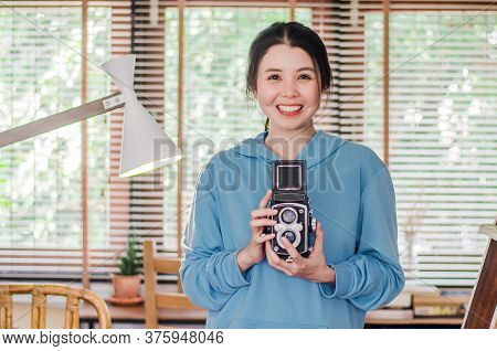 Stylish Vintage Smiling Female Photographer Holding Her Old Twin Lens Camera To Her Chest As She Com