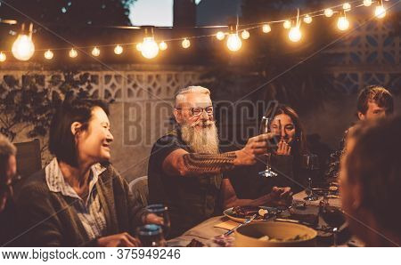 Happy Family Dining And Tasting Red Wine Glasses In Barbecue Dinner Party - People With Different Ag