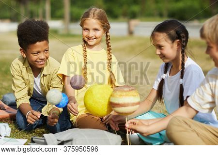 Multi-ethnic Group Of Kids Sitting On Green Grass And Holding Model Planets While Enjoying Outdoor A