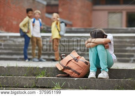 Full Length Portrait Of Crying Schoolgirl Sitting On Stairs Outdoors With Group Of Teasing Children