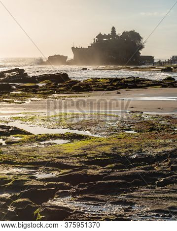Backlit Outline Of Pura Tanah Lot Balinese Sea Temple With Crashing Waves On The Pebble Beach, Denpa