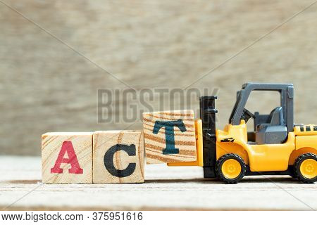Toy Forklift Hold Letter Block T To Complete Word Act On Wood Background