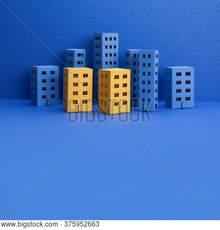 Miniature City With Blue Yellow Paper Houses On Blue Background. Abstract Urban Architecture Landsca
