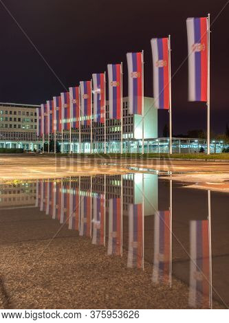 Flags Of Serbia Reflecting In The Puddle Of Water At Night, In Front Of The Palace Of Serbia Buildin
