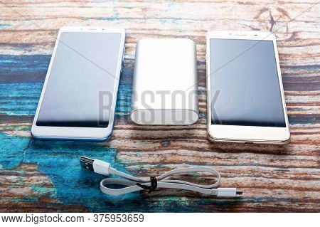 Smartphones And Power Bank At An Angle. Angled View.