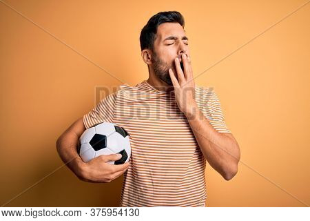 Handsome player man with beard playing soccer holding footballl ball over yellow background bored yawning tired covering mouth with hand. Restless and sleepiness.