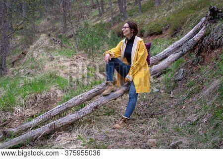 Woman In Yellow Raincoat Resting In Forest After Hike. Woman Hiking In Nature On Tara Mountain In Se