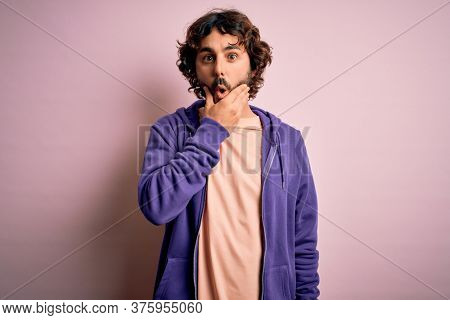 Young handsome sporty man with beard wearing casual sweatshirt over pink background Looking fascinated with disbelief, surprise and amazed expression with hands on chin