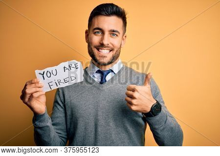 Young handsome man holding paper with you are fired message over yellow background happy with big smile doing ok sign, thumb up with fingers, excellent sign