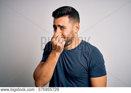 Young handsome man wearing casual t-shirt standing over isolated white background smelling something stinky and disgusting, intolerable smell, holding breath with fingers on nose. Bad smell