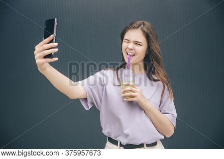 Young Stylish Trendy Woman Isolated Over Grey Blue Background. Wonderful Girl Taking Selfie And Maki