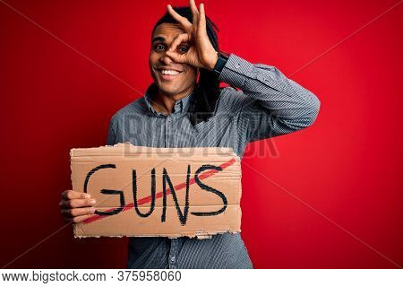 Young african american man with dreadlocks holding banner doing prohibited guns protest with happy face smiling doing ok sign with hand on eye looking through fingers