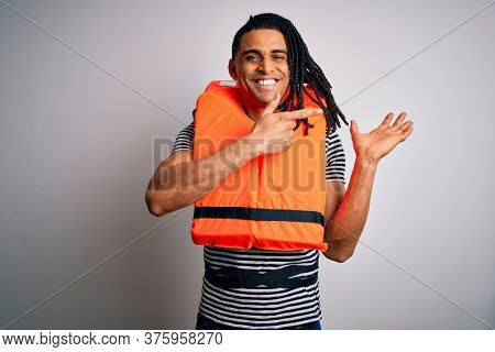Young african american afro man with dreadlocks wearing orange lifejacket amazed and smiling to the camera while presenting with hand and pointing with finger.
