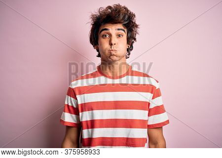 Young handsome man wearing striped casual t-shirt standing over isolated pink background puffing cheeks with funny face. Mouth inflated with air, crazy expression.