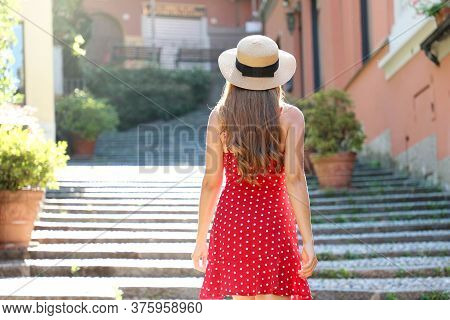 Travel In Italy. Back View Of Tourist Girl Climbs The Stairs In Bellagio, Italy. Young Traveler Woma