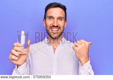 Young handsome man drinking glass of water to refreshment over isolated purple background pointing thumb up to the side smiling happy with open mouth