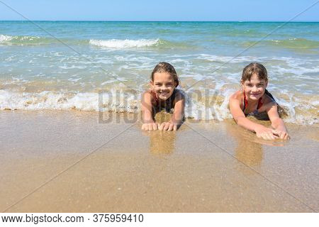 Girls Lie On The Sand Of The Sea Coast And Happily Look At The Frame