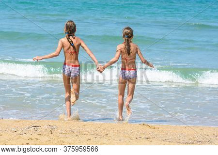 Girls Holding Hands Run Into The Sea