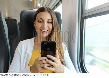 Smiling Business Woman Using Smartphone Social Media App While Commuting To Work In Train. Young Wom