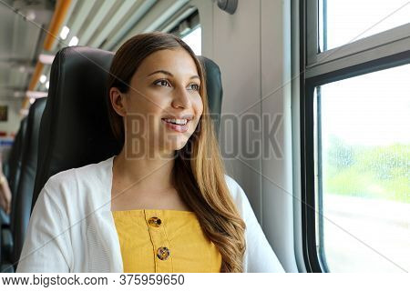 Portrait Of Young Woman Looking Through The Train Window. Happy Train Passenger Traveling Sitting In