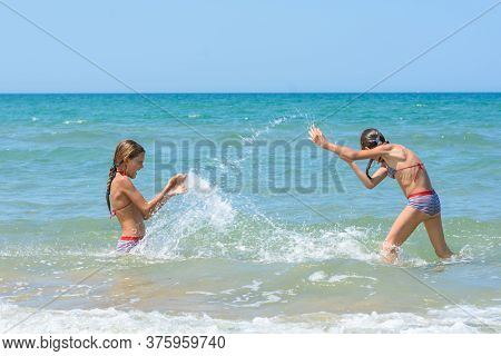 Girls Splash On Each Other On The Sea Coast