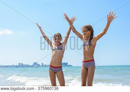 Two Girls Joyfully Raised Their Hands Up On The Sea On Vacation And Swimming