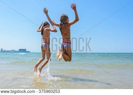 Two Girls Joyfully Bounce On The Seashore