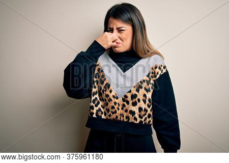 Young beautiful woman wearing casual sweatshirt standing over isolated white background smelling something stinky and disgusting, intolerable smell, holding breath with fingers on nose. Bad smell