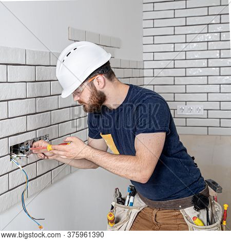 Electrician Builder At Work, Installation Of Sockets And Switches. Professional In Overalls With An