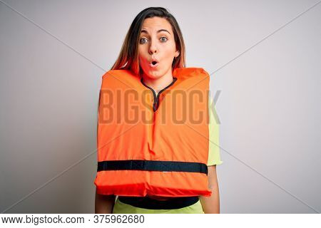 Young beautiful blonde woman with blue eyes wearing orange lifejacket over white background afraid and shocked with surprise expression, fear and excited face.