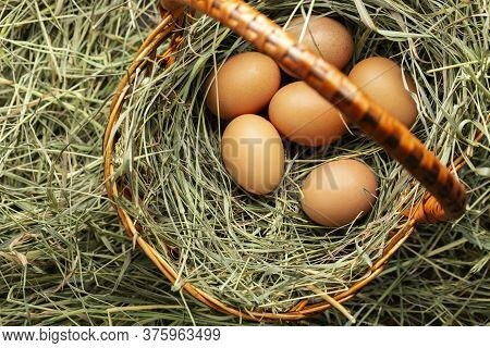 Basket With Chicken Eggs In The Hay. View From Above.