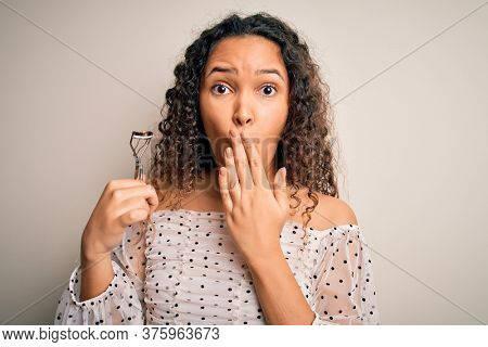 Young beautiful woman with curly hair holding eyelases curler over white background cover mouth with hand shocked with shame for mistake, expression of fear, scared in silence, secret concept