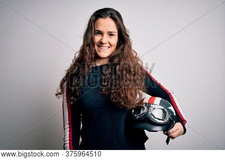 Beautiful motorcyclist woman with curly hair holding moto helmet over white background with a happy face standing and smiling with a confident smile showing teeth