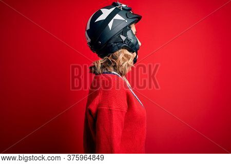 Middle age beautiful blonde motorcyclist woman wearing moto helmet over red background looking to side, relax profile pose with natural face with confident smile.