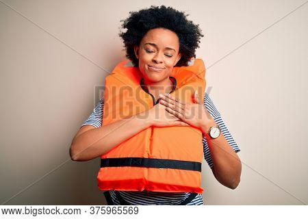 Young African American afro woman with curly hair wearing orange protection lifejacket smiling with hands on chest with closed eyes and grateful gesture on face. Health concept.